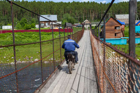 A motorcyclist rides an off-road motorcycle on a suspended wooden bridge over a mountain river.