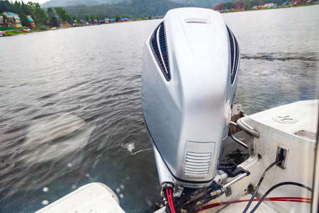 Motor boat engine while sailing on a lake with waves of water from movement. Travel, vacation, leisure and hobbies, fishing.
