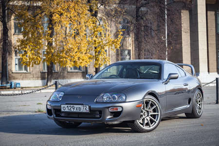 Novosibirsk, Russia - 10.09.2019: A very rare Japanese sports car in the back of a Toyota Supra coupe in gray with a high spoiler on the road in the city near trees with yellow leaves.