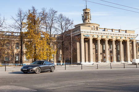 Novosibirsk, Russia - 10.09.2019: A rare Japanese sports car in the back of a gray Toyota Supra coupe with a spoiler on the road in city near trees with yellow leaves and an old building with columns.