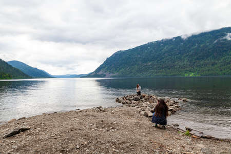 Altai, Russia - 08.01.2018: Two young girls take pictures of each other against the backdrop of a picturesque place on the shore of the Teletskoye lake during travel and excursions in the nature reser