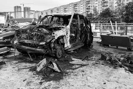 A burnt car after a fire or an accident in a parking lot covered with rust and black coal with scattered spare parts around. Robbery, arson, terrorism.
