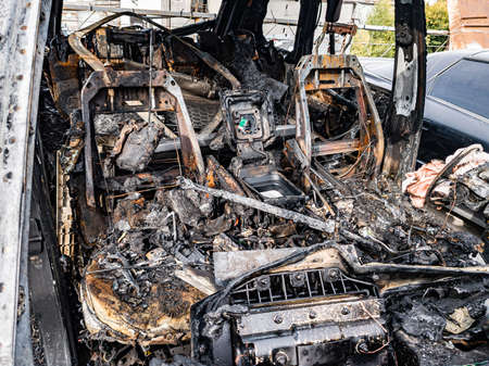 A burnt car interior after a fire or an accident in a parking lot covered with rust and black coal with scattered spare parts around. Robbery, arson, terrorism.