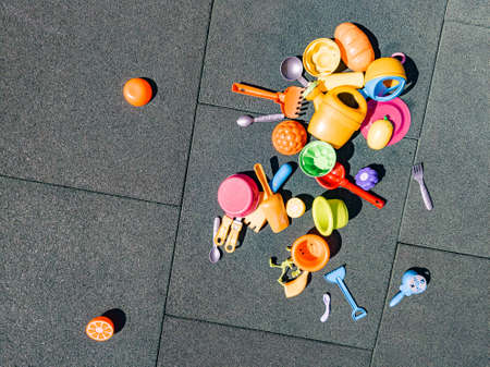 A lot of multi-colored childrens toys on the playground with a rubber coating in the courtyard. Forks, spoons, rakes, scoops, plastic dishes. Childhood and carefree life, youth.