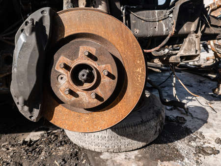 A close-up on the old rusty brake system of a car with pads, discs, a caliper on a lift in a vehicle repair workshop. Auto service industry. Stock Photo