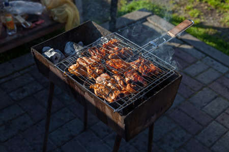 Close-up on the process of cooking shashlik of pork or beef meat clamped in a grill with a crispy burnt crust over gray burnt coals on an open fire with smoke going up. Stock fotó