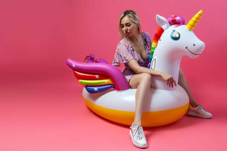 A blonde girl in a sexy sundress with slim legs in white sneakers sits on an inflatable multi-colored unicorn on a pink isolated background and look down. Summer vacation at the beach and travel.