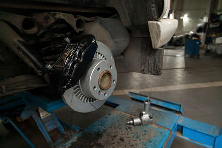 The braking system of the car with the wheel removed with the disc, pads, hub and cooling holes during maintenance and replacement in the workshop on the vehicle repair. Auto service industry.
