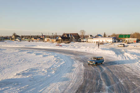 Novosibirsk, Russia - 02.02.2019: Old Russian cars Lada 2104 prepared for racing drive on the ice on a frozen lake, drifting and moving in a skidder in a turn on a specially cleared track