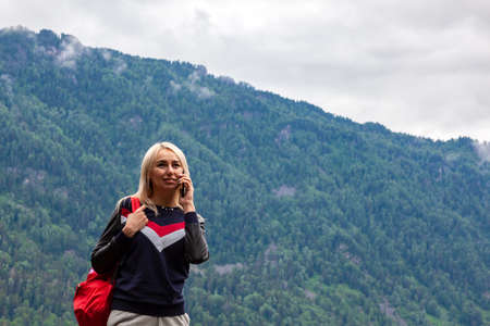 Beautiful young blonde woman who is standing on the rocky shore of Lake Teletskoye with a red backpack during an excursion in the Altai mountains and making call to her friends. Travel and tourism.