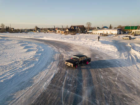 Novosibirsk, Russia - 02.02.2019: Old Russian car Lada 2106 prepared for racing drive on the ice on a frozen lake, drifting and moving in a skidder in a turn on a specially cleared track