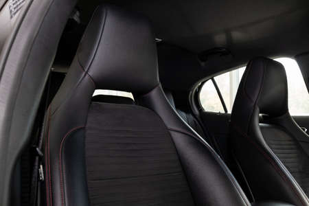 Close-up on the front sport car seats with black leather trim, lateral support and fabric inserts, of used vehicle in after detailing and dry cleaning. Auto service industry.