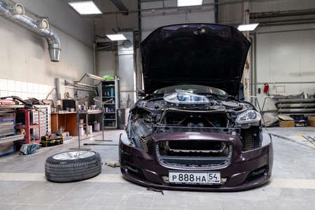 Novosibirsk, Russia - 11.07.2019: The brown car in the body of the sedan is preparing for painting the body without headlights and bumper in a workshop for repair vehicles. Auto service industry.
