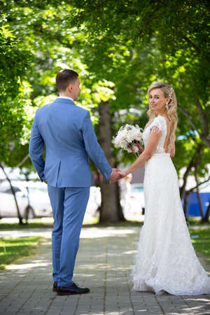 Young beautiful couple of newlyweds bride and groom walk holding hands in a park with green trees on their wedding day. Love and lovestory of wife and husband before starting a family. 스톡 콘텐츠
