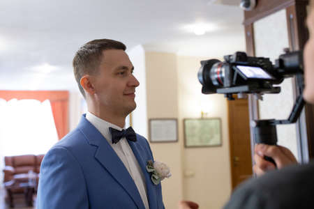 Videography of the wedding ceremony with the groom in a blue suit using the camera, operator and stabilizer. Stok Fotoğraf