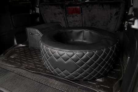 Car spare wheel sheathed in a black leather case and diamond-shaped stitching with white thread in the trunk of an SUV with a tool bag on a rubber mat. Auto service industry. Stock Photo