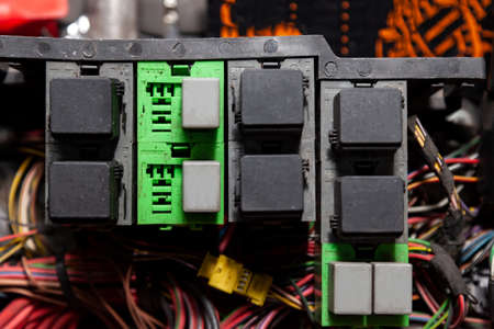 Fuse box and black relay in the car's electrical circuit during vehicle repair in the workshop. Auto service industry.