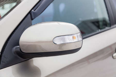 Close-up of the side left mirror with turn signal repeater and window of the car body beige SUV on the street parking after washing and detailing in auto service industry. Road safety while driving Stock Photo