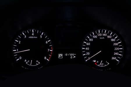 Il cruscotto dell'auto si illumina di bianco con le frecce di notte con un tachimetro, un contagiri e altri strumenti per monitorare le condizioni del veicolo in stile moderno su sfondo nero isolato