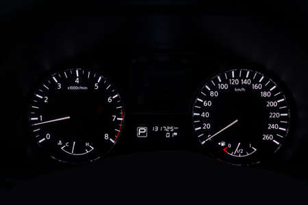 The dashboard of the car is glowing white with arrows at night with a speedometer, tachometer and other tools to monitor the condition of the vehicle in modern style on black isolated background