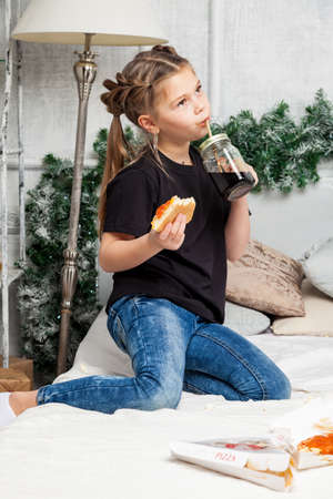 Little cute beautiful girl sits cross-legged on a bed in blue jeans and a black shirt eating pizza and drink against the background of a room in the New Years decoration with a Christmas tree. Reklamní fotografie