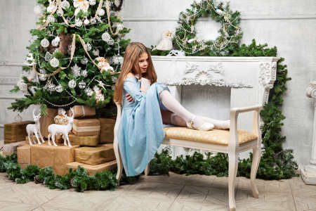 Little cute beautiful girl a bench near the Christmas tree and fireplace and writes a letter to Santa Claus against the background of a room in the decoration with a New Year 2020 tree.Child dream.