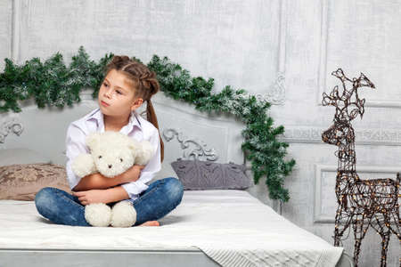 Little cute beautiful girl sits cross-legged on a bed in blue jeans and a white shirt hugging a soft teddy bear toy against the background of a room in the New Years decoration with a Christmas tree.