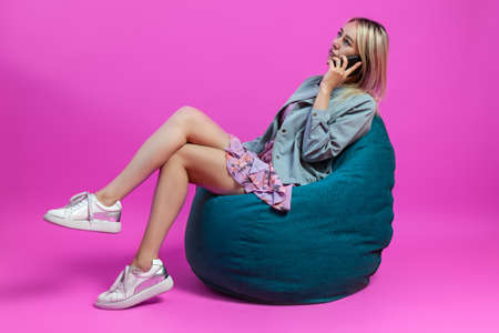 Beautiful blonde girl in a blue jacket and a purple sundress sits on a green bag chair with her legs folded on a pink isolated background and talking on the phone with a smartphone to her ear Reklamní fotografie