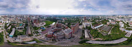 Aerial view of the city with traffic, streets and buildings with green trees and rails under the blue sky with clouds at summer day in Novosibirsk. Panoramic 360 degrees of the panet. Reklamní fotografie