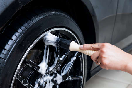 A male worker washes a black car with a special brush for cast wheels and scrubs the surface to shine in a vehicle detailing workshop. Auto service industry. Stok Fotoğraf