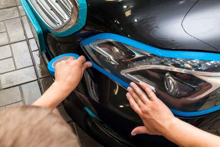 Un hombre de apariencia caucásica con cinta de papel azul enyesa un faro de elemento de carrocería con un automóvil negro para pulir una pintura y barnizar y eliminar rasguños en un taller de lavado y detallado de vehículos.