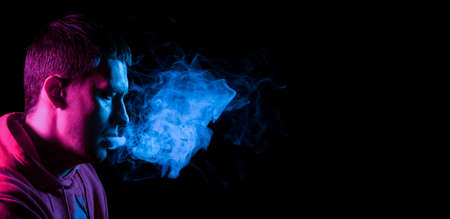 Close up portrait of the face of an adult serious man exhales blue toxic smoke while smoking e-cigarette and vape illuminated with pink colored light on a black background. Harm to health. Imagens