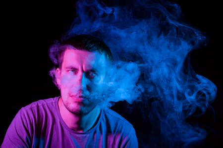Close up portrait of the face of an adult serious man exhales blue toxic smoke while smoking e-cigarette and vape illuminated with pink colored light on a black background. Harm to health.