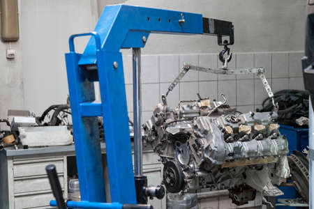 Used v8 engine with eight cylinders suspended mounted on a crane for overhaul repair and installation on a car after a breakdown in the vehicle workshop. Auto service industry. Ð¡ylinder scratches.