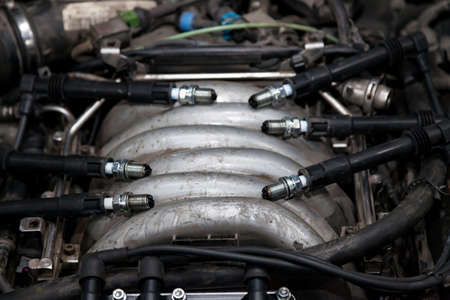 Spark plugs with high voltage wires on the engine under the hood of a car during diagnosis and repair in a workshop for vehicles. Auto service industrial. Banco de Imagens