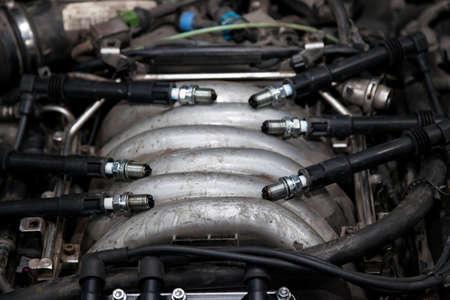 Zündkerzen mit Hochspannungskabeln am Motor unter der Motorhaube eines Autos während der Diagnose und Reparatur in einer Werkstatt für Fahrzeuge. Autoservice industriell. Standard-Bild