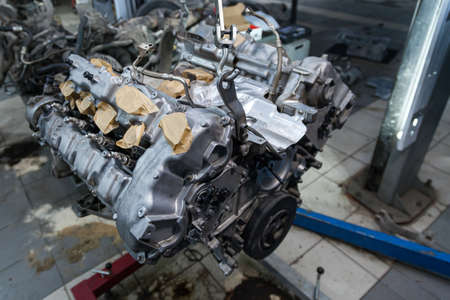 Used v8 engine with eight cylinders suspended mounted on a crane for overhaul repair and installation on a car after a breakdown in the vehicle workshop. Auto service industry. Ð¡ylinder scratches. Stock Photo