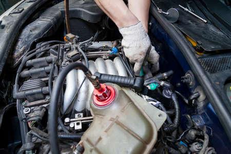 Un riparatore di auto svita le parti con una chiave inglese con una maniglia verde nel vano motore come candele e bobine di accensione in un'officina di riparazione di veicoli. Industria dei servizi automobilistici.