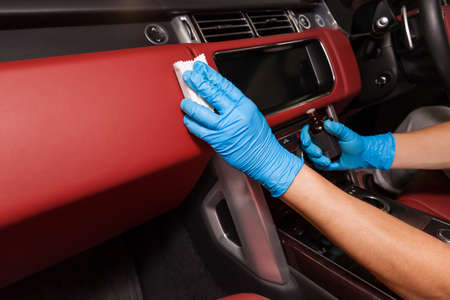 Applying a nano-ceramic coating for interior leather on the car's seat red upholstery by a worker in blue gloves with a sponge and bottle of chemical composition. Auto service industry.