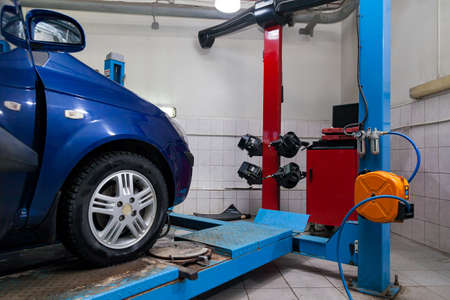 Blue car front wheel view stands on the stand wheel alignment convergence of the car during regular maintenance in the workshop for repair of vehicles . Auto service industry. Imagens