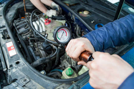 Pressure build-up in a tank with antifreeze for forcing air plugs in the engine cooling system replacing the fluid using a pump with a pressure scale in a car repair workshop. Auto service industry.