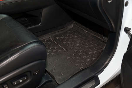 Dirty car floor mats of black rubber under passenger seat in the workshop for the detailing vehicle before dry cleaning. Auto service industry. Interior of sedan.
