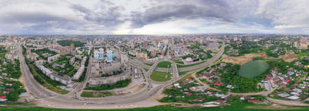 Aerial view of the city with traffic, streets and buildings with green trees and rails under the blue sky with clouds at summer day in Novosibirsk. Panoramic 360 degrees of the planet.