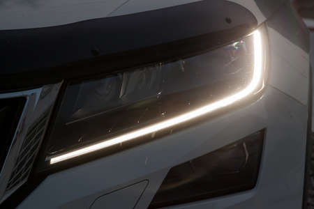 Front headlamp view of white car with  turn on led day running DRL light and bi-xenon lens