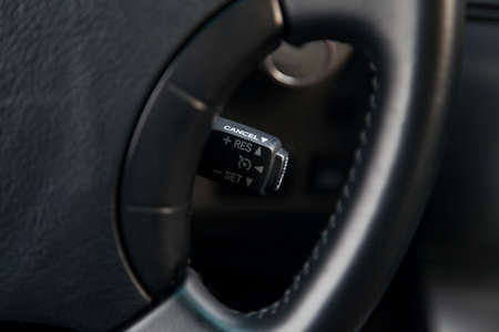 The shift lever to set the automatic cruise control speed inside the car close-up located near the steering wheel in black with white signs and symbols of beautiful design in interior. Auto service.