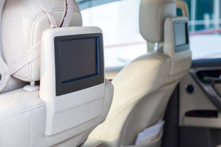 Entertainment system for rear passengers in a car with two monitors mounted on the backs of the front seats for watching TV, cartoons and computer games.