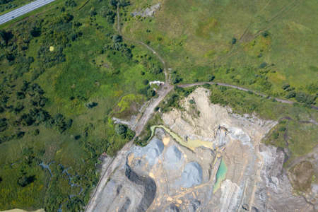 Aerial view of a small plant for the production and cleaning rubble and cement near the heaps of building materials, the tractors and trucks transports the finished product. Mining in quarry.