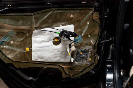 Repair of the car body black crossover in the service station, the restoration of the cabin. The side door trim panel was removed, the sound system wiring was replaced, handle and lock seeing. Stock Photo
