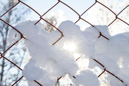 A close-up on an iron fence net with snow flakes frozen to it and the sun's rays shining through the winter afternoon.