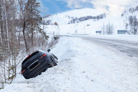 Accident on a winter snowy track with a black car skidding and falling into a ditch due to ice. Safety and poor driving on the road. Reklamní fotografie